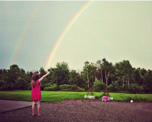 little girl touching a rainbow